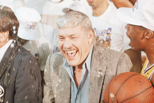 Los Angeles Lakers owner Jerry Buss gets doused with champagne by members of his team.