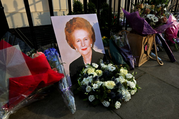 A portrait of former Prime Minister Margaret Thatcher is left next to floral tributes outside her residence in London.