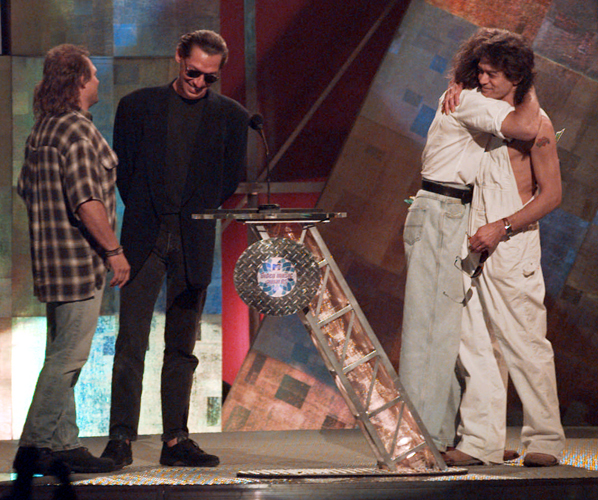 Former Van Halen bandmates David Lee Roth and Eddie Van Halen, right, embrace as they are reunited onstage at the MTV Video Music Awards in 1996. Bandmates Michael Anthony, left, and Alex Van Halen are also present.