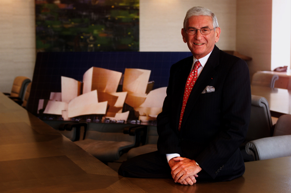 Eli Broad in 2000. Behind him is a photo of the Walt Disney Concert Hall design.