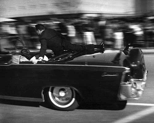 The presidential limousine, a 1961 Lincoln Continental, races toward Parkland Hospital, with Secret Service Agent Clinton Hill clinging to the back.