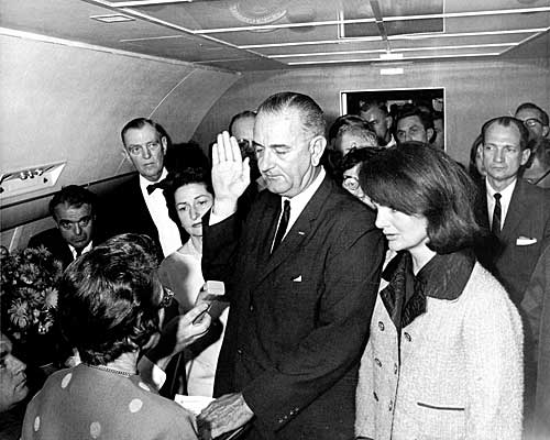 With Jacqueline Kennedy beside him, Vice President Lyndon B. Johnson is sworn in as president by U.S. District Judge Sarah T. Hughes, left.