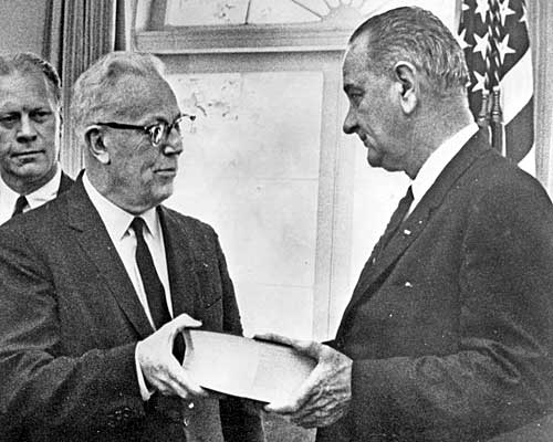 Warren gives President Johnson a report on the assassination of President John F. Kennedy. Looking on is Warren Commission member and Michigan Rep. Gerald Ford. Ford will become president after Richard Nixon, the man Kennedy defeated, resigns the presidency 10 years later.