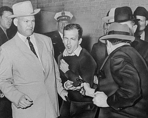 Plainclothesman Jim A. Leavelle, left, recoils as Jack Ruby shoots Oswald.