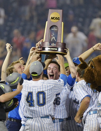 UCLA closer David Berg stands in front of teammate Ryan Deeter while holding the NCAA championship trophy following their 8-0 victory over Mississippi State in Game 2 of the College World Series on Tuesday.