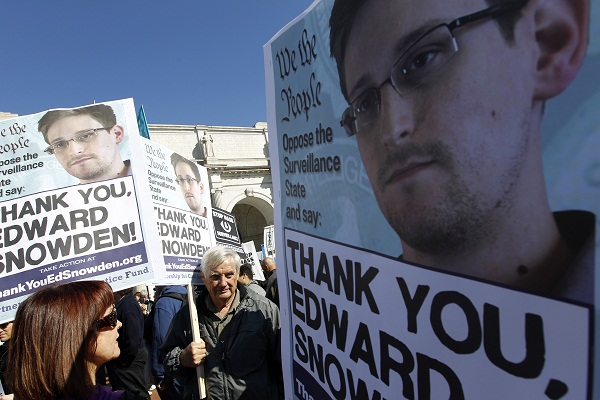 Demonstrators protest U.S. surveillance practices with signs applauding NSA leaker Edward Snowden.