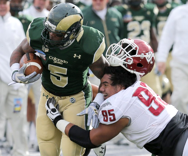 Washington State nose tackle Ioane Gauta loses his helmet as he hits Colorado State running back Kapri Bibbs. Bibbs rushed for three touchdowns in the Rams' 48-45 win over the Cougars.
