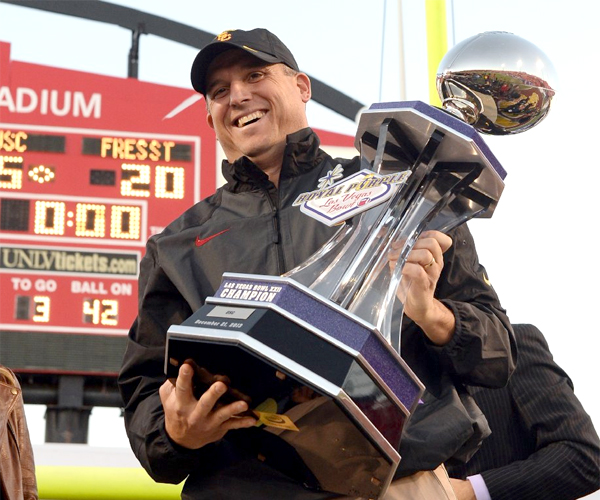USC Interim Coach Clay Helton holds the championship trophy after defeating Fresno State, 45-20, in the Royal Purple Las Vegas Bowl.