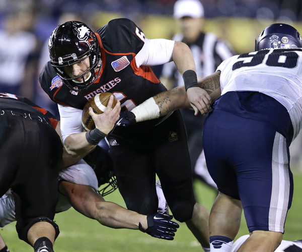 Northern Illinois quarterback Jordan Lynch plows through the Utah State defense for a first down. The Aggies held Lynch and Co. to two touchdowns in a 21-14 victory.