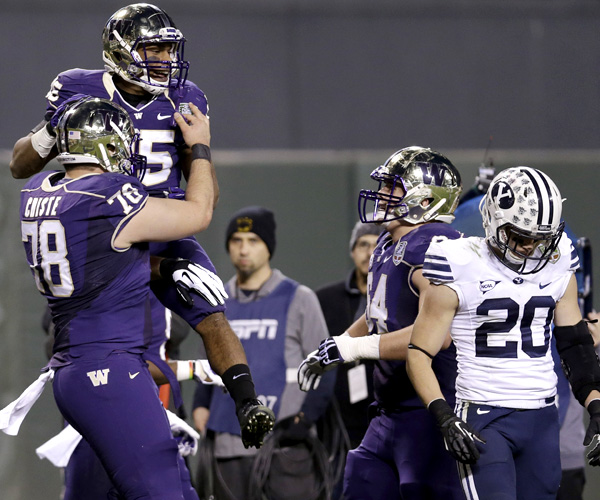 Washington running back Bishop Sankey is lifted by teammate Mike Criste after rushing for a touchdown against BYU in the first half of the Fight Hunger Bowl at AT&T Park in San Francisco.