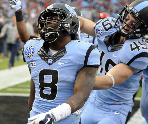 North Carolina's T.J. Logan (8) is congratulated by teammate Mikey Bart after returning a kickoff 78 yards for a touchdown against Cincinnati in the first quarter of the Belk Bowl at Bank of America Stadium.