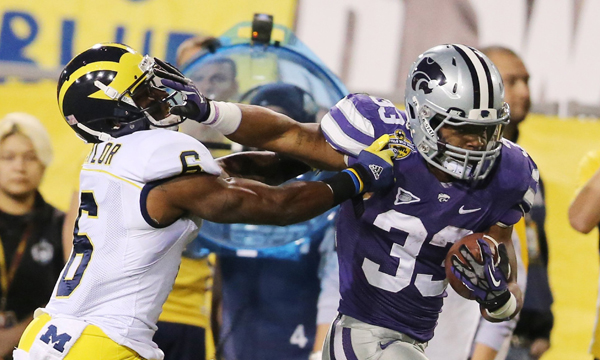 Kansas State running back John Hubert, right, stiff arms Michigan defensive back Raymon Taylor on a run during the Wildcats' 31-14 victory in the Buffalo Wild Wings Bowl. Hubert finished with 80 yards rushing and a touchdown in the win.
