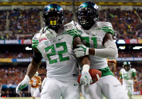 Oregon linebacker Derrick Malone, left, celebrates with teammate Tony Washington after returning an interception for a touchdown in the Ducks' 30-7 win over Texas at the Alamo Bowl in San Antonio, Texas.