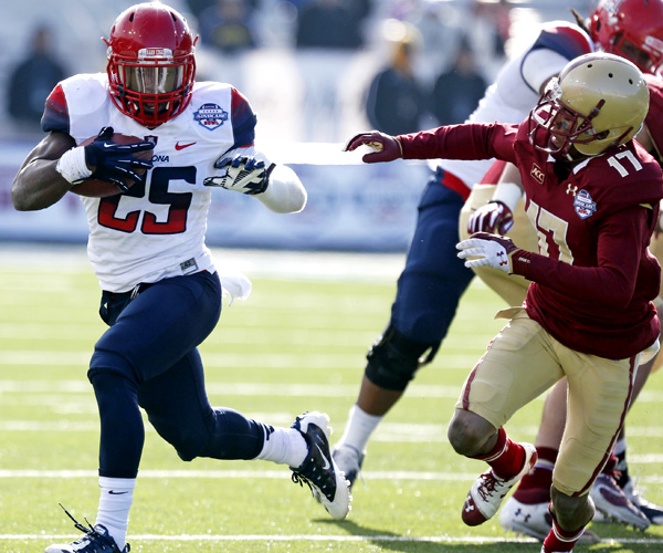 Arizona running back Ka'Deem Carey, who rushed for 169 yards and two touchdowns, evades Boston College defensive back Bryce Jones in the second half of the AdvoCare V100 Bowl.