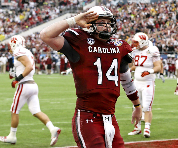 South Carolina quarterback Connor Shaw salutes fans after catching a touchdown on a pass from receiver Bruce Ellington in the first half of the Capital One Bowl. Shaw, the game's MVP, also passed for three touchdowns and ran for another.