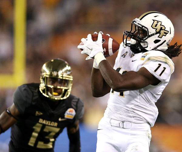 Central Florida receiver Breshad Perriman catches a pass for a 34-yard gain against Baylor defensive back Terrell Burt to help set up a touchdown in the first quarter of the Tostitos Fiesta Bowl.