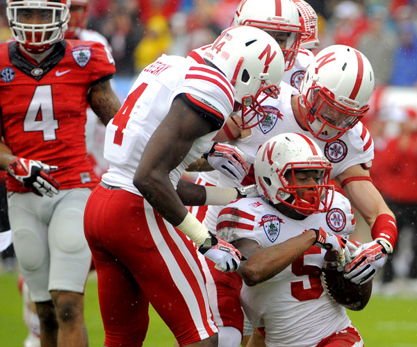 Nebraska cornerback Josh Mitchell (5) celebrates with teammates after recovering a fumbled kick return by Georgia in the first half of the Gator Bowl. Tommy Armstrong Jr. connected with Quincy Enunwa for two touchdowns, including a 99-yarder in the third quarter, for the Cornhuskers.