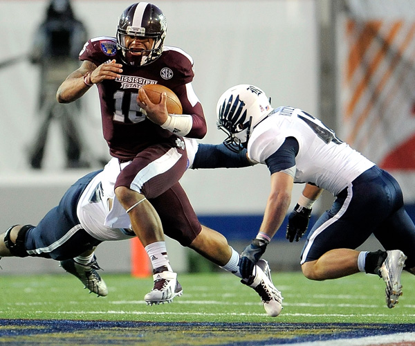 Mississippi State quarterback Dak Prescott, who threw three touchdown passes and ran for two more scores, avoids the tackle attempt by Rice's Michael Kutzler during the Liberty Bowl.