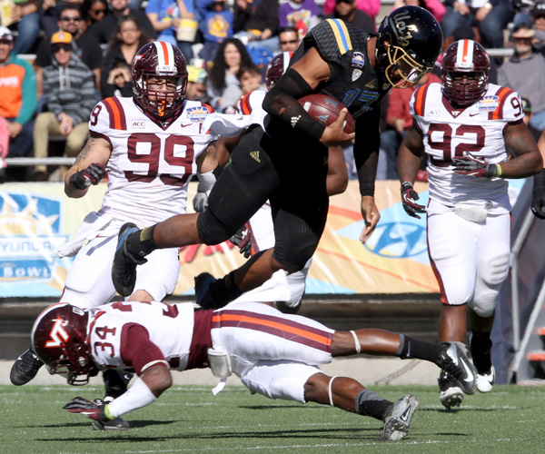 Bruins quarterback Brett Hundley, who passed for 226 yards and two touchdowns as well as rushed for 161 yards and two scores, is tripped by Virginia Tech safety Kyshoen Jarrett in the second quarter of the Sun Bowl.