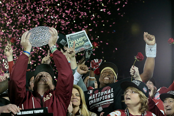 Florida State Coach Jimbo Fisher hoists The Coaches' Trophy as he celebrates with his family and quarterback Jameis Winston following the Seminoles' 34-31 win over Auburn for the BCS title at the Rose Bowl.