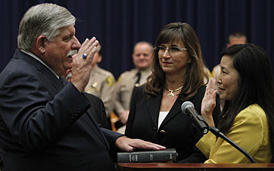 John L. Scott takes the oath of office, administered by Sachi Hamai, executive officer of the L.A. County Board of Supervisors. Alice Scott, center, watches as her husband is sworn in as Los Angeles County sheriff.