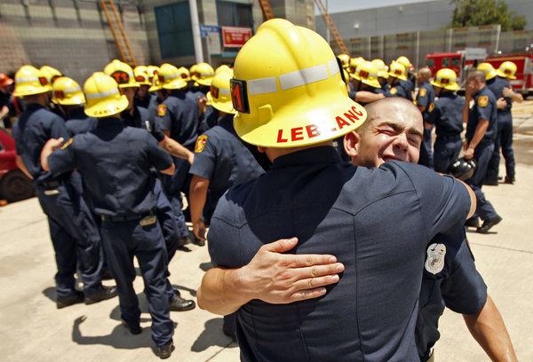 Daniel Balzano, right, gets a hug from Matthew LeBlanc as recruits celebrate following a graduation ceremony on June 12