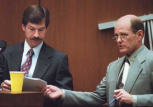 FBI Special Agent Roger Martz, left, reviews a document with defense lawyer Robert Blasier.