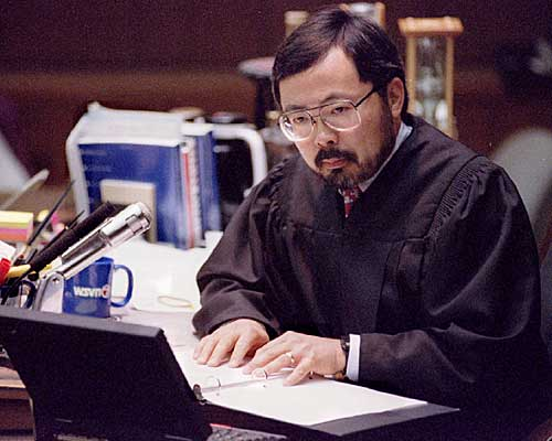 Judge Lance Ito reads from a notebook as he instructs the jury regarding the law and how they are to deliberate.