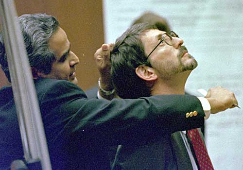 Dr. Lakshmanan Sathyavagiswaran, Los Angeles County coroner, grips the hair of prosecutor Brian Kelberg and uses a ruler to demonstrate how Nicole Brown Simpson's throat may have been slashed.