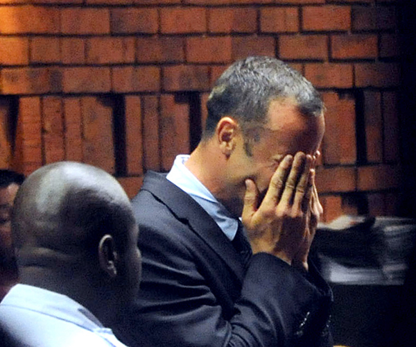 Pistorius hides his face in his hands during a bail hearing.