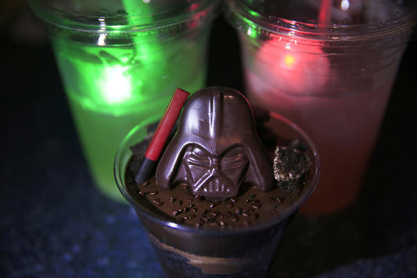 A Darth by Chocolate desert, center, next to The Dark Side drink, on right, and the Light Side drink. It includes a souvenir light-up Millennium Falcon as featured during the media preview of Star Wars Season of The Force at Disneyland.