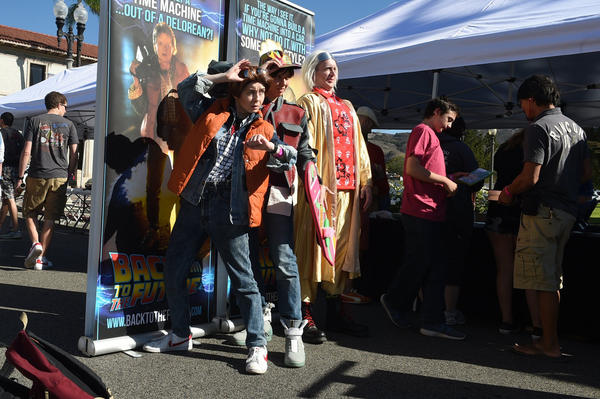 """Back To The Future"" fans, from left, Shannon Burckhard, Kathy Degoutrie and Markus Geiberger pose in front of posters during Fillmore's celebration of the movie franchise on Thursday, Oct. 22, 2015."