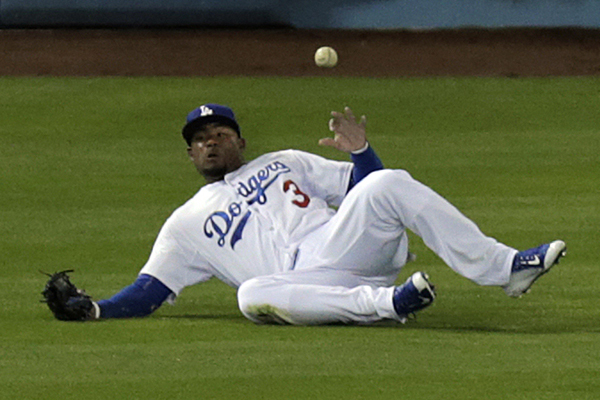 Dodgers left fielder Carl Crawford can't make a sliding catch on a run-scoring triple by Padres left fielder Justin Upton during the first inning.