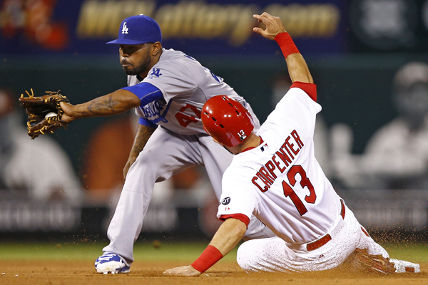 Cardinals' Matt Carpenter steals second base, beating the tag of Dodgers second baseman Howie Kendrick during the fifth inning of the Dodgers' 3-0 loss.