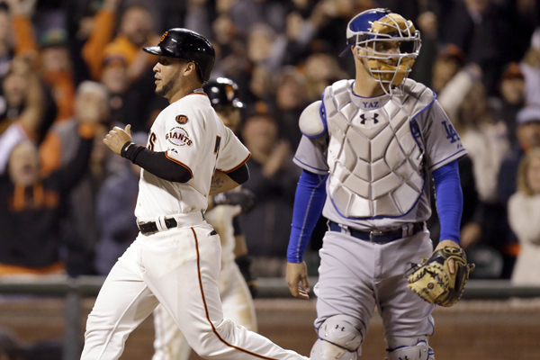 San Francisco Giants pinch runner Gregor Blanco, left, scores the winning run behind Dodgers catcher Yasmani Grandal in the ninth inning of a 3-2 victory.