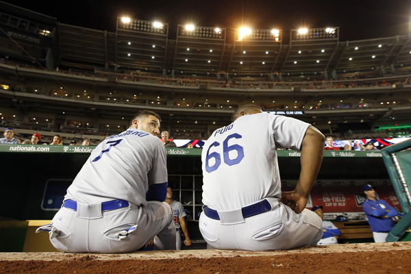 Dodgers teammates Alex Guerrero, left, and Yasiel Puig wait for the stadium lights to be turned back on during a game against the Washington Nationals on July 17, 2015.