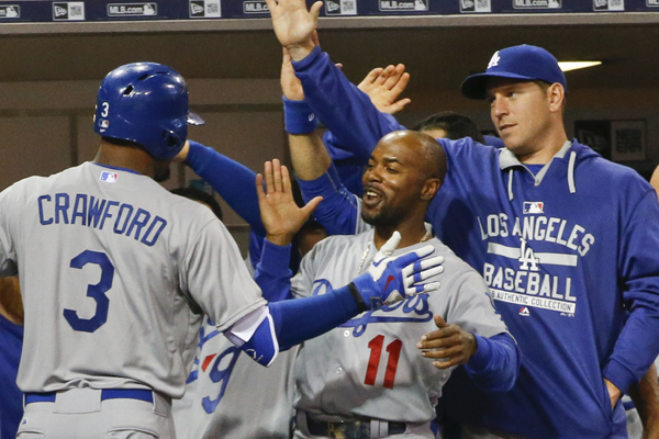 Dodgers left fielder Carl Crawford, left, is congratulated by teammates Jimmy Rollins, center, and A.J. Ellis after hitting a solo home run during the seventh inning of a 3-0 victory over the San Diego Padres.