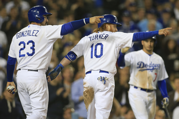 Dodgers first baseman Adrian Gonzalez, left, and third baseman Justin Turner point to Andre Ethier (not pictured) after he drove them in on a two-run double in the fourth inning against the Braves.