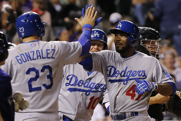 Dodgers second baseman Howie Kendrick, right, celebrates with teammate Adrian Gonzalez after hitting a three-run home run in the eighth inning of a win over the Colorado Rockies.