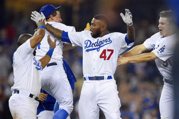 Dodgers second baseman Howie Kendrick, center, celebrates with his teammates after hitting a walk-off single in the ninth inning against the Arizona Diamondbacks.