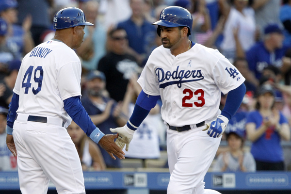 Dodgers third base coach Lorenzo Bundy, left, congratulates first baseman Adrian Gonzalez after his solo home run during the fourth inning of a win over the San Francisco Giants.