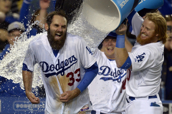 Dodgers left fielder Scott Van Slyke is doused with water by teammate Justin Turner after hitting a walk-off three-run home run against the Miami Marlins.