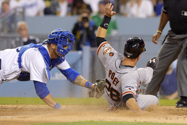 San Francisco Giants catcher Buster Posey, right, beats the tag by Dodgers catcher Yasmani Grandal to score during the seventh inning of the Dodgers' loss.