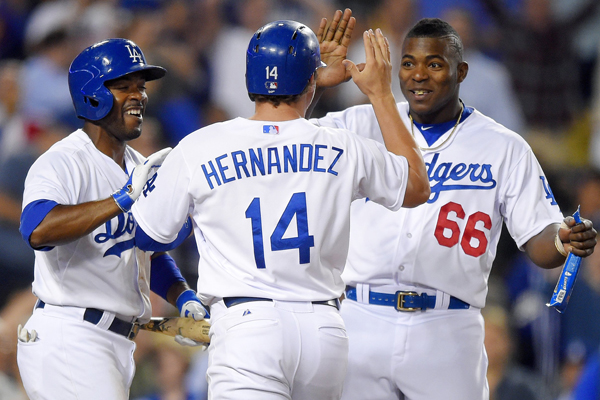 Dodgers' Enrique Hernandez, center, celebrates with teammates Yasiel Puig, right, and Jimmy Rollins after scoring the winning run on a balk in the ninth inning of a win over the Texas Rangers.