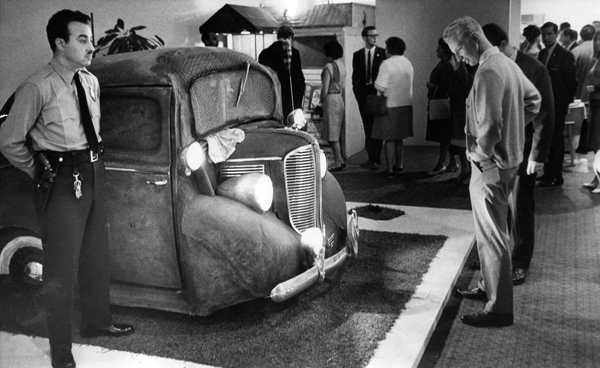 "A museum guard stands behind artist Edward Kienholz's ""Back Seat Dodge '38."""