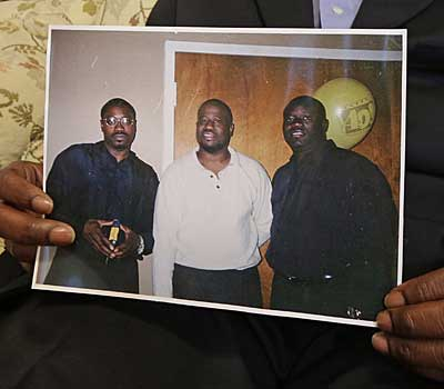 Anthony Scott holds a photo of himself, center, and his brothers Walter, left, and Rodney.
