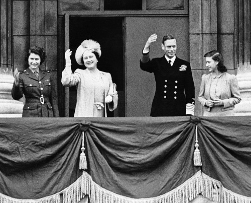 From left to right, Princess Elizabeth, Queen Elizabeth, King George and Princess Margaret stand on a balcony at Buckingham Palace on May 8, 1945, and wave to Londoners celebrating the announcement of Germany's unconditional surrender.