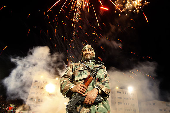 A member of the government security forces is on duty amid a fireworks display in Zawiya.