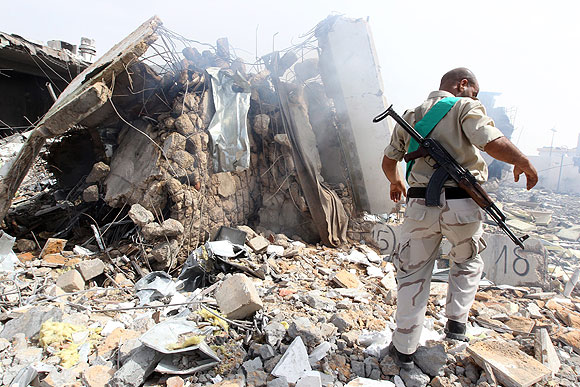 A Libyan soldier stands in a Tripoli compound belonging to Moammar Kadafi that was hit by NATO airstrikes.