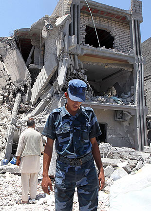 A Libyan policeman inspects rubble in front of a damaged house.